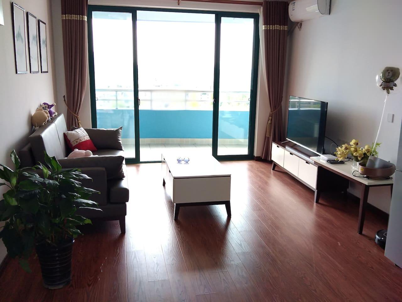 客厅配有电视 沙发 茶几 餐桌等家具,从客厅阳台可以看到陆家嘴金融中心。