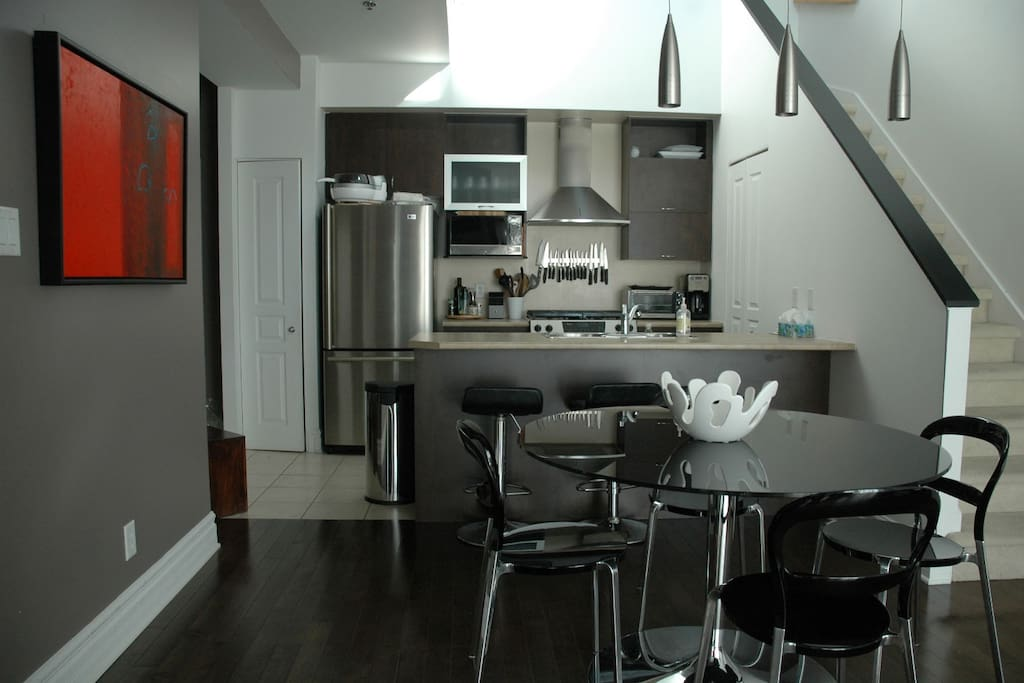 Kitchen with bar and two stools. Dinning room seating 6 people comfortably.
