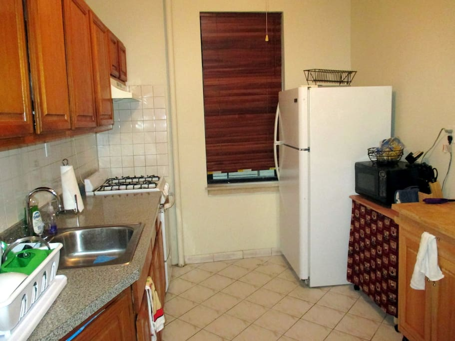 Large kitchen with ample counter-space, microwave, stove, oven, fridge, dishware.