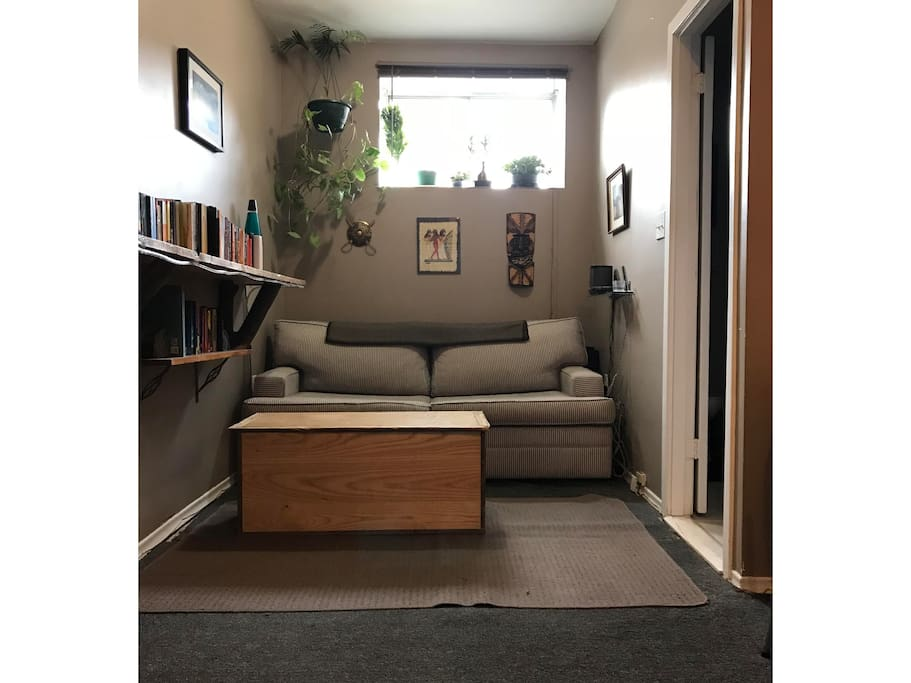 The middle section of the living area, adjacent to the dining nook, has a sofa bed, plenty of books and plants.