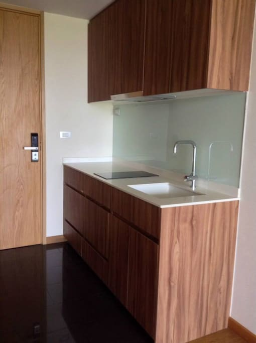 open kitchen with fridge, cooker, washing machine with dryer