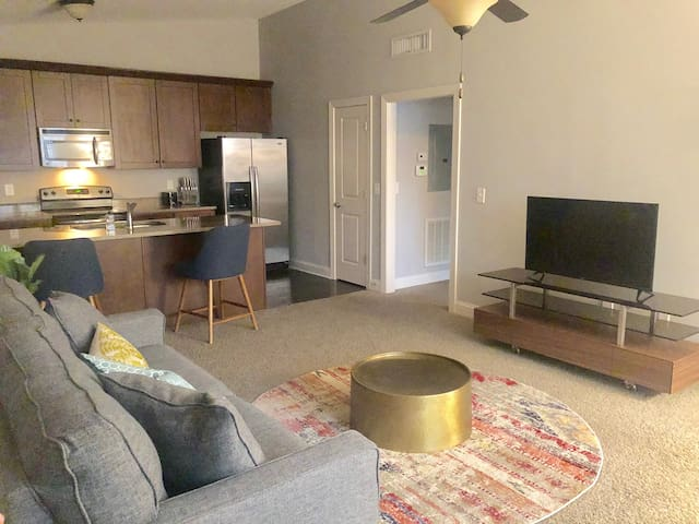 Living room attached to fully furnished kitchen with barstools for dining on the granite breakfast bar.