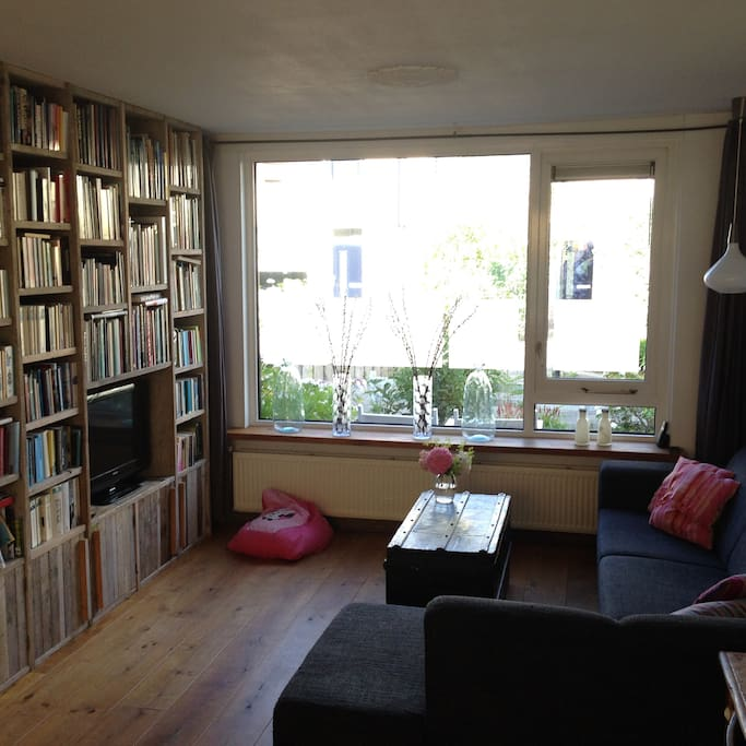 huiskamer met grote hoekbank en fraaie boekenkast