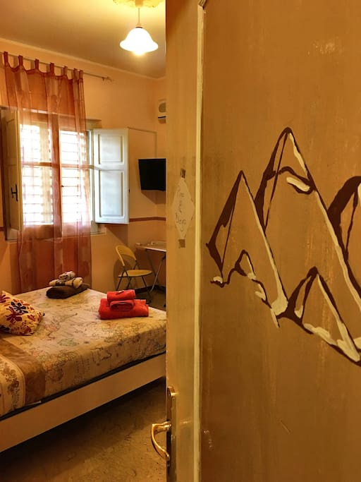 il Cairo è una camera matrimoniale dotata di bagno privato, aria condizionata, TV. come per le altre camere della Casa è arredata a tema// Cairo is a double room with bathroom, air conditioner and TV. Like the other rooms in the house this is also decorated with theme.