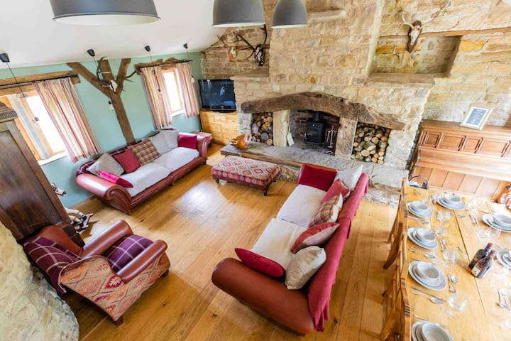 Large comfortable living space with dining table that can seat 10. View is from the upstairs mezzanine area. Logs provided for log burner.