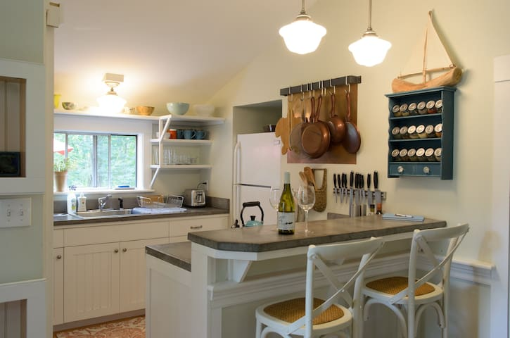When you walk in, you are in the living room, and this custom kitchen with concrete countertops is on the left. Through the kitchen is the bath, with a sliding barn-like door into it.