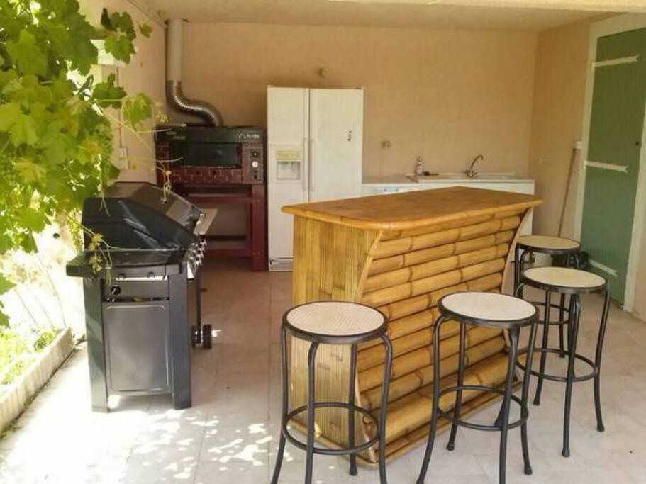 La cuisine d'été avec son coin bar, plancha, four à pizza, frigo américain...