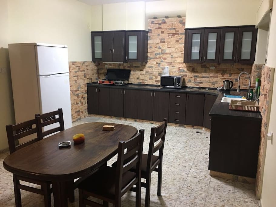 Kitchen with big fridge, microwave, kettle, gas hub and dining table