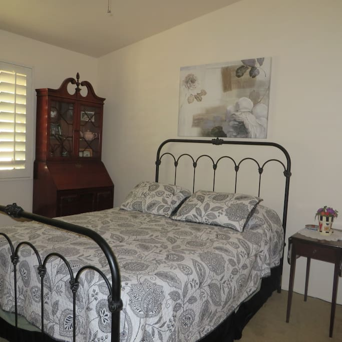 Pillow top queen bed with plantation shutters and ceiling fan keep the antique room restful and comfortable.