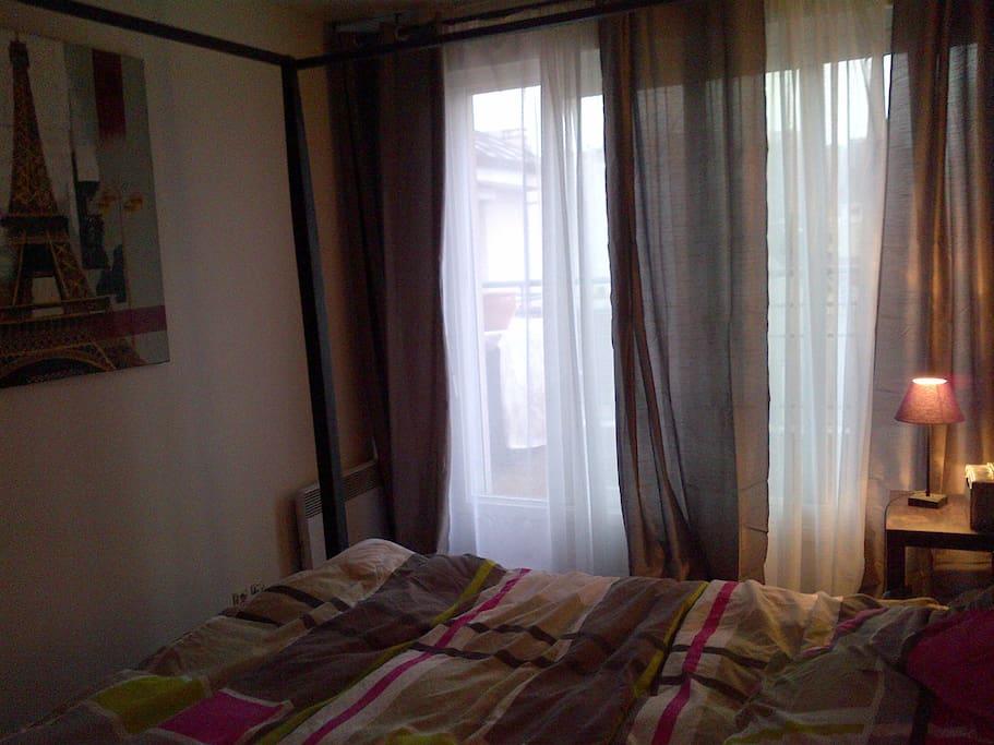 porte fenêtre donnant sur la terrasse et tour Eiffel