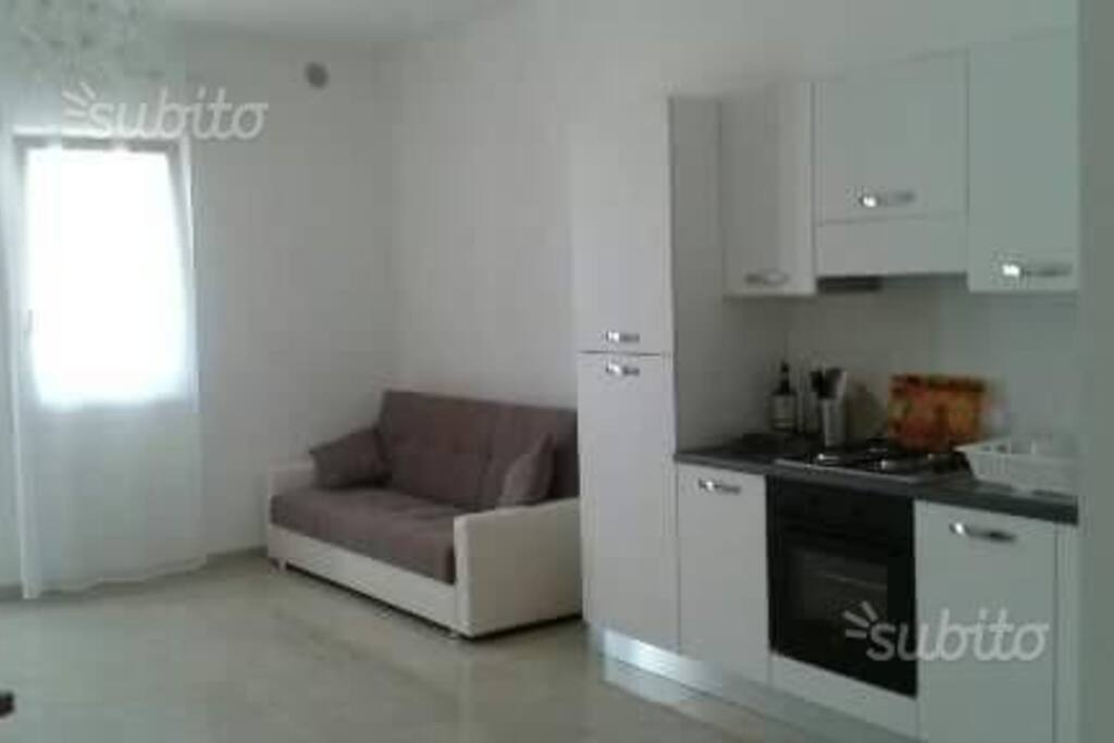 ingresso con divano letto, soggiorno e cucina