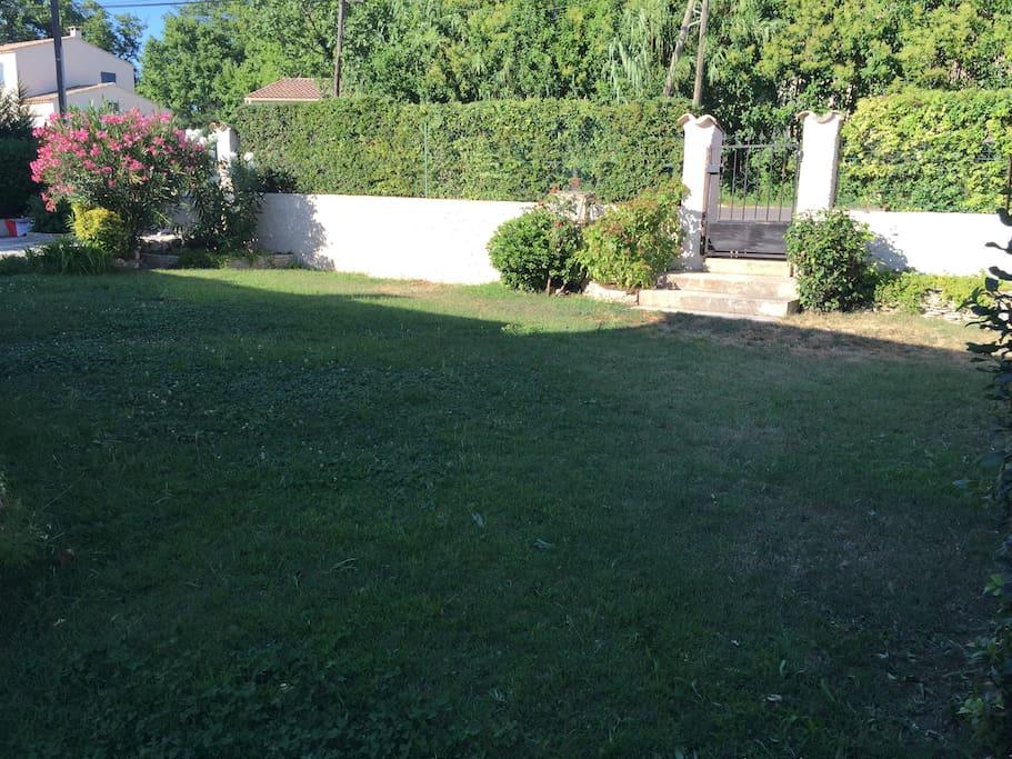 Le jardin qui donne devant l'entrée de la maison.