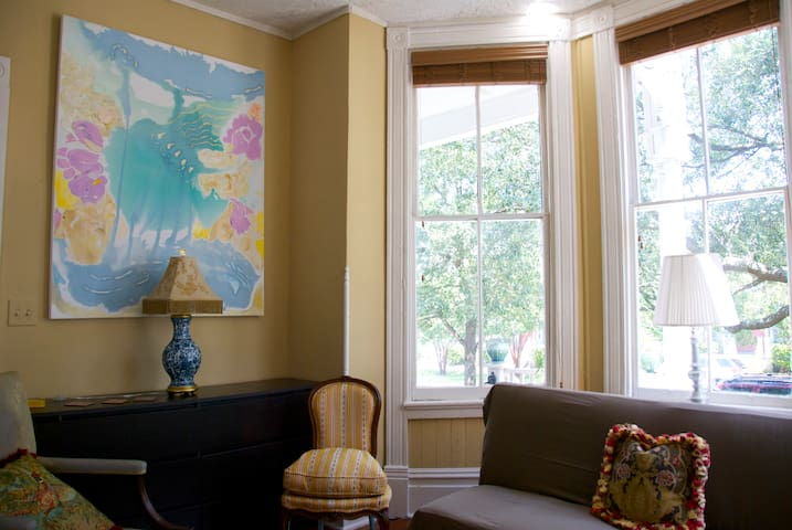 The bay window provides panoramic views of the tree lined street and ample natural light.
