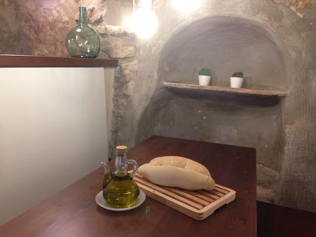 Mesa de la cocina al lado de un mueble hecho por nuestros antepasados en la misma pared de la muralla. Antiguamente servía para dejar los botijos de agua para abastecer la casa pues antes no había agua corriente.