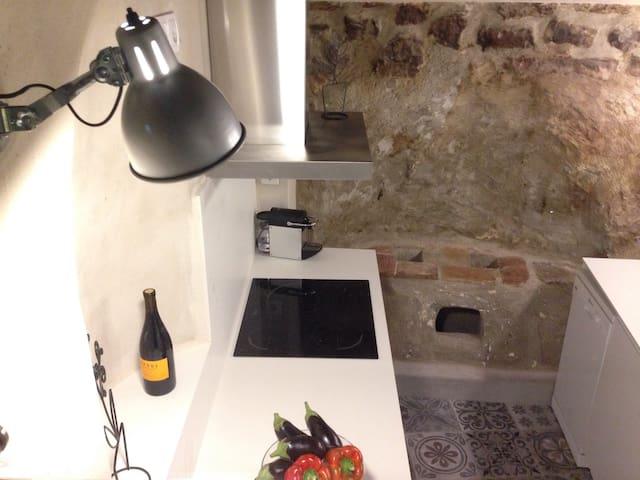 Zona de fuegos de la cocina. Se sitúa al lado de la antigua cocina hecha sobre la misma muralla. Antes se cocinaba con brasas que calentaban las paellas. Por eso la piedra de la pared de esta zona parece volcánica.