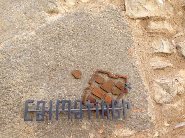 Logotipo de la casa en hierro ubicado en la puerta principal de acceso a la casa. El logotipo representa la antigua población enmurallada con sus 4 antradas fortificadas y con una X sobre la muralla se marca Cal Matiner que de las 4 paredes 1 es muralla.