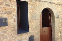 Vista de la entrada. La puerta principal se divide en dos recordando las antiguas puertas. Ello permite dar luz natural a la planta baja junto con la nueva ventana realizada que tratándose de una nueva actuación se ha hecho con marco de hierro para diferenciarlo debidamente.