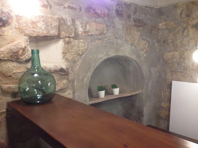 Barra de la cocina. Debajo se encuentra la zona de agua corriente incluido lavaplatos. Se observa el mueble  integrado con la muralla donde antiguamente se ponían los botijos.