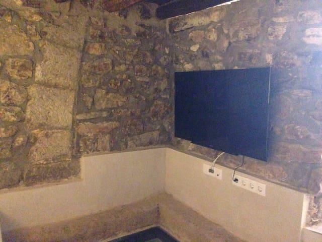 Televisión del salón donde empieza el arco de las antiguas caballerizas de defensa de la población medieval.