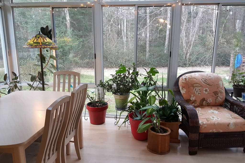 Sunroom overlooks pool and includes a table and chairs for a quiet work space or dining.
