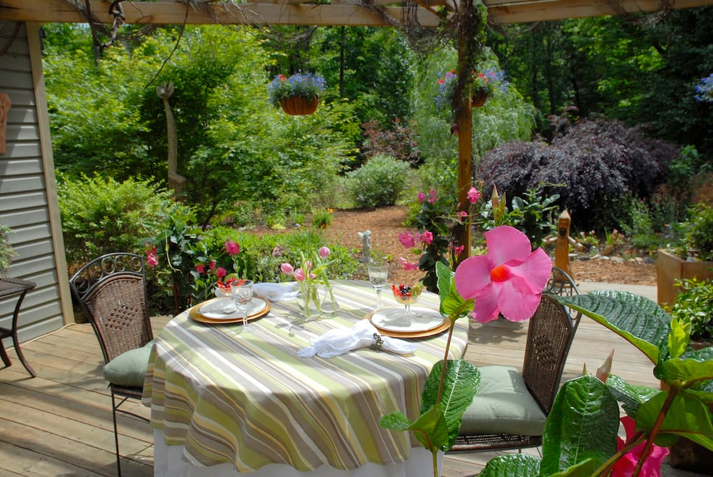 Charming outdoor seating with a gorgeous view of the gardens and forest
