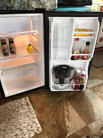 Fridge has water filter, ketchup, mustard , syrup, hot sauce and complementary beverages.