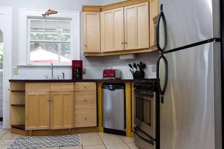 The kitchen features stainless steel appliances as well as basic cooking utensils.