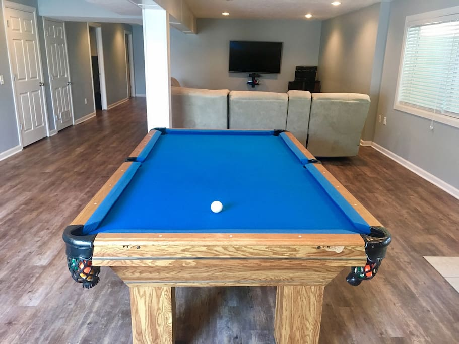The basement complete with regulation size pool table, couch with recliners built in, a Smart TV, stereo system, and PS4.