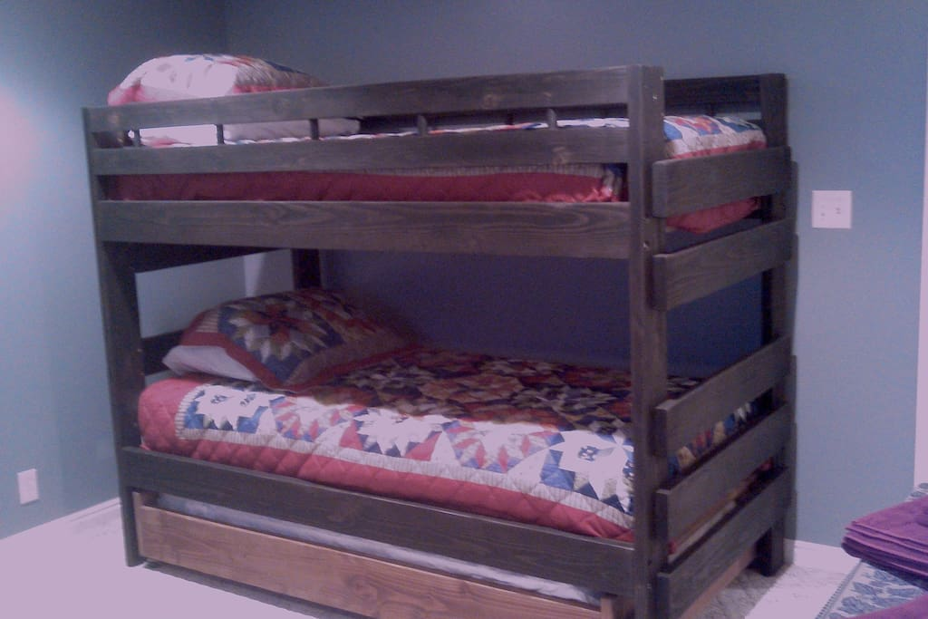 Bunks are made from solid wood and are rated to hold 300# per platform. The trundle under the bottom bunk accommodates another guest.