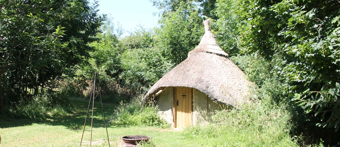 Thatched roundhouse in the woods.
