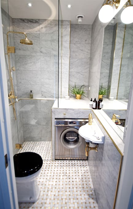 "Bathroom. Lavish bathroom (completely renovated 2015) in classical Victorian style with carrara marble and gold details throughout. Heated floors, large inset mirror and combined washer-dryer machine of the exclusive brand ""Smeg""."