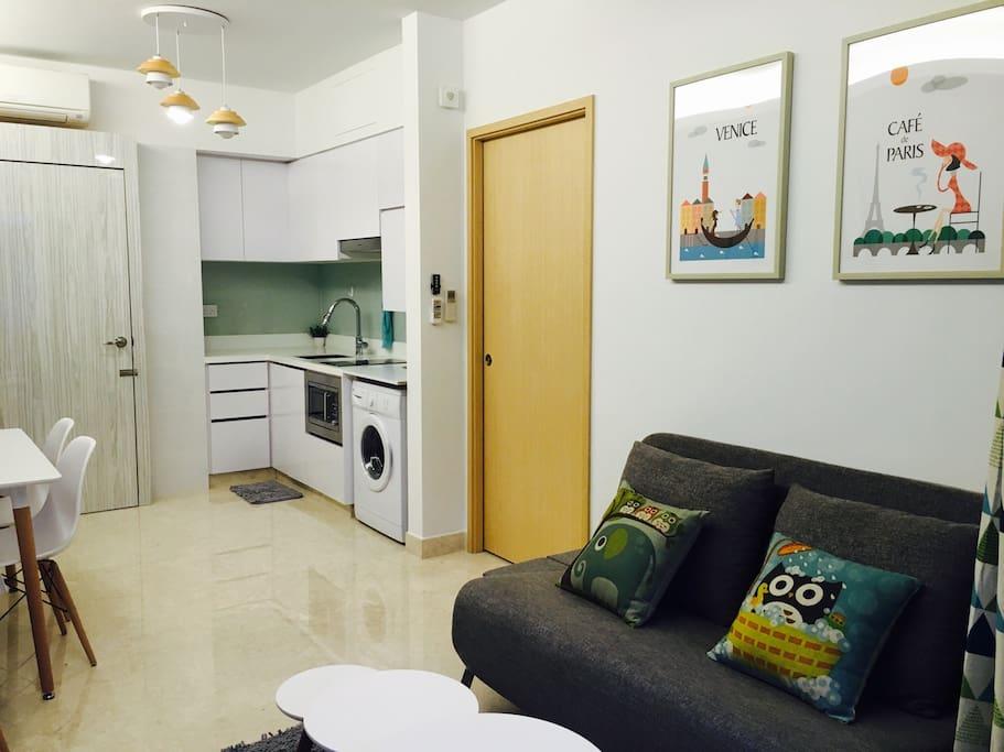 Queen sofa bed, kitchen, brown master bedroom door and white main door.