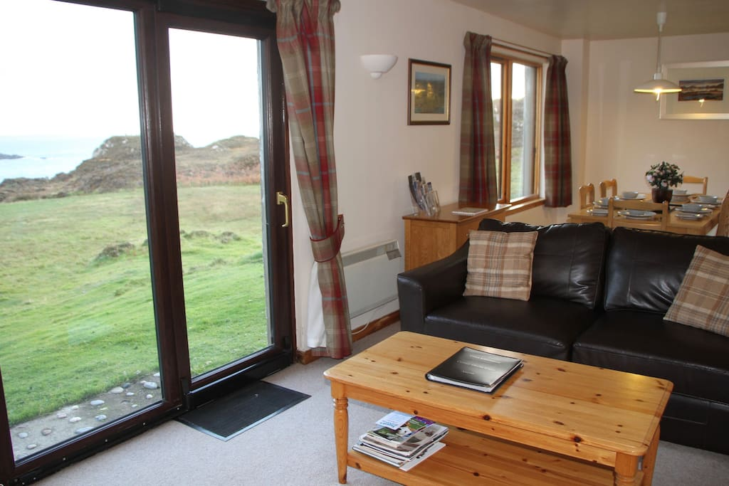 Comfortable and spacious living area with French windows leading to an outside seating area