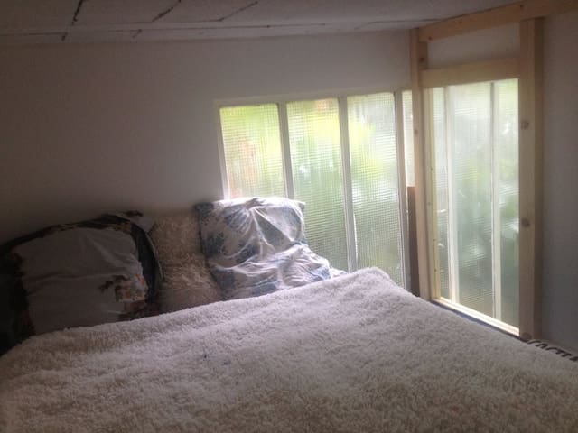 Bedroom with windows over the threes.