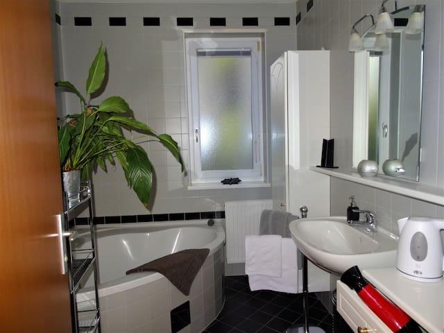 Badezimmer mit Eckbadewanne, Haarföhn, Wasserkocher und Kühlschrank - Bathroom with corner bath, hair dryer, kettle and fridge