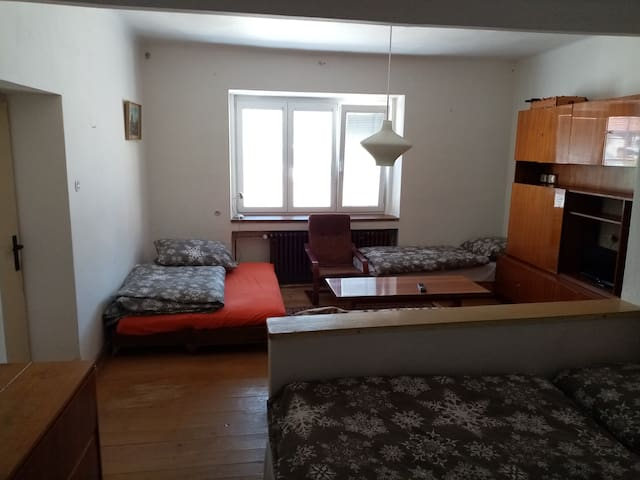 Prostorný pokoj pro hosty, neprůchozí, situovaný na severní stranu, vyhled z okna na náměstí, spaní pro šest osob, satelitní TV, skříně, stůl, židle, pohovka