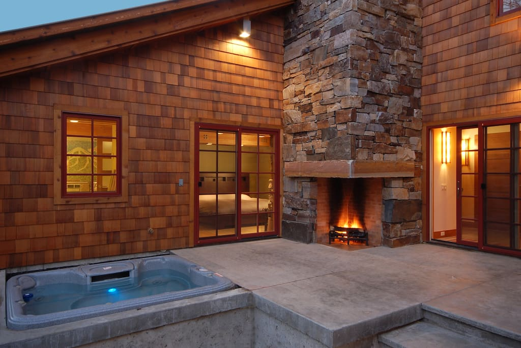 Patio with hot tub and outdoor fireplace