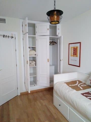 Dormitorio desde la ventana, amplio, con armario empotrado de tres puertas.