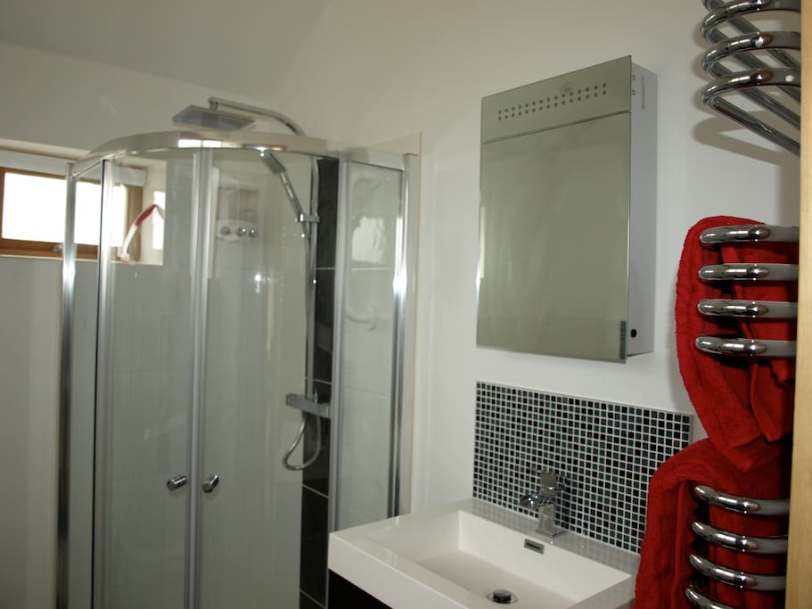 Ample bathroom with corner bath and walk in shower, heated towel rad