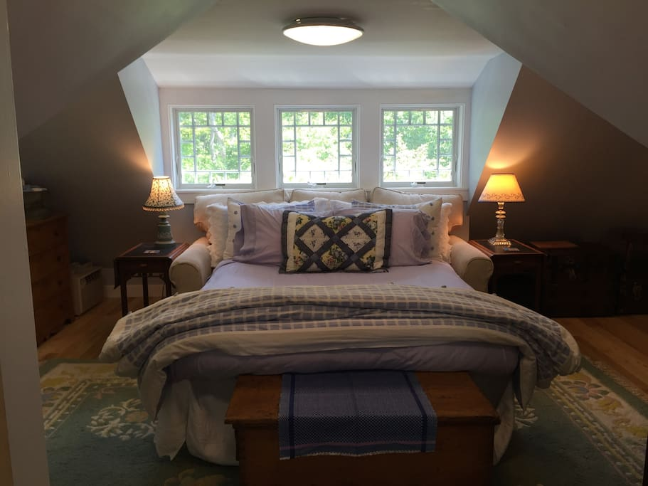 The cozy queen size bed has a mattress topper and is tucked under a dormer featuring Queen Ann style windows.
