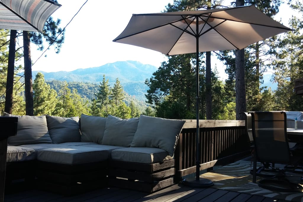 View of the mountains from the main deck. Couch, dining table, and grill.