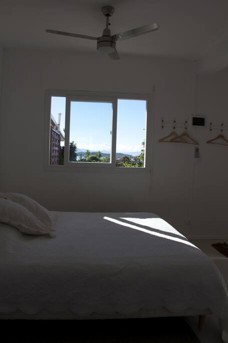 fenêtre et brasseur d'air au-dessus de lit pour les chaudes nuits d'été