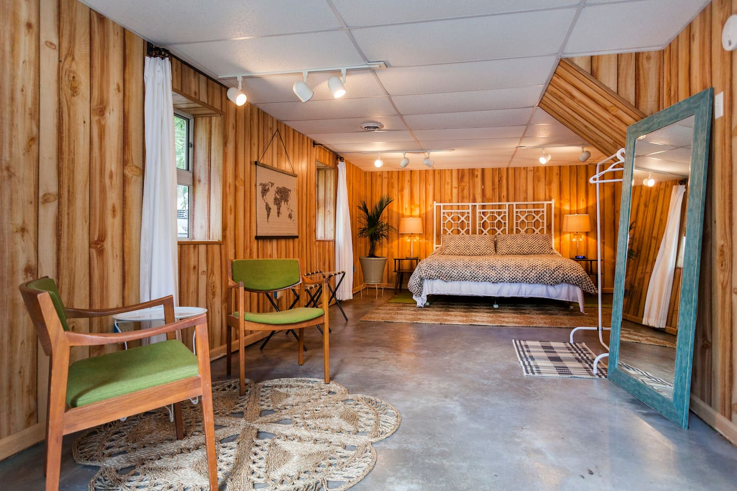 We've gone a little island and a little retro. The stained and sealed concrete is hip and clean, and rugs soften up the underfoot experience. The bed is king sized and we've been told by guests that its heavenly.