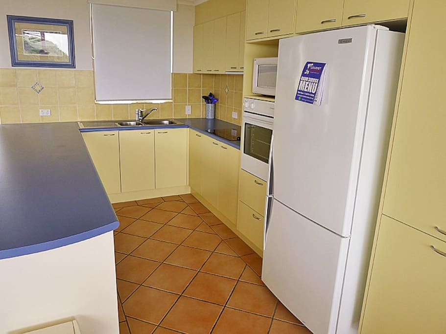 The kitchen is fully stocked with everything you need, including a cooktop, oven, full-sized fridge/ freezer and dishwasher