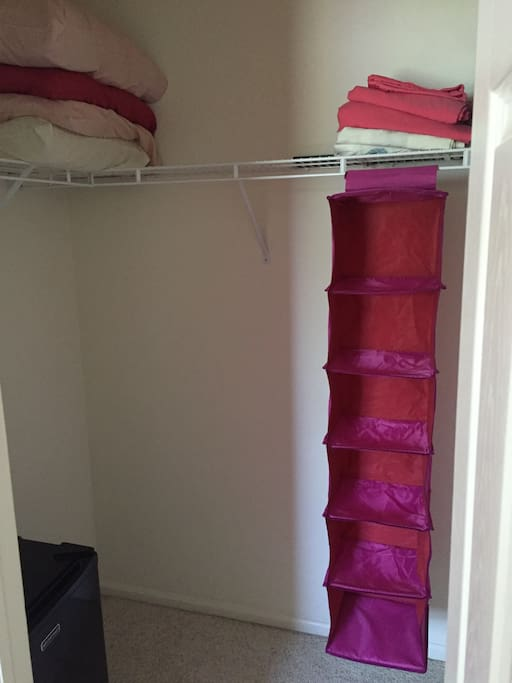A walk in closet with a mini fridge, extra sheets and pillows and an additional twin air bed!