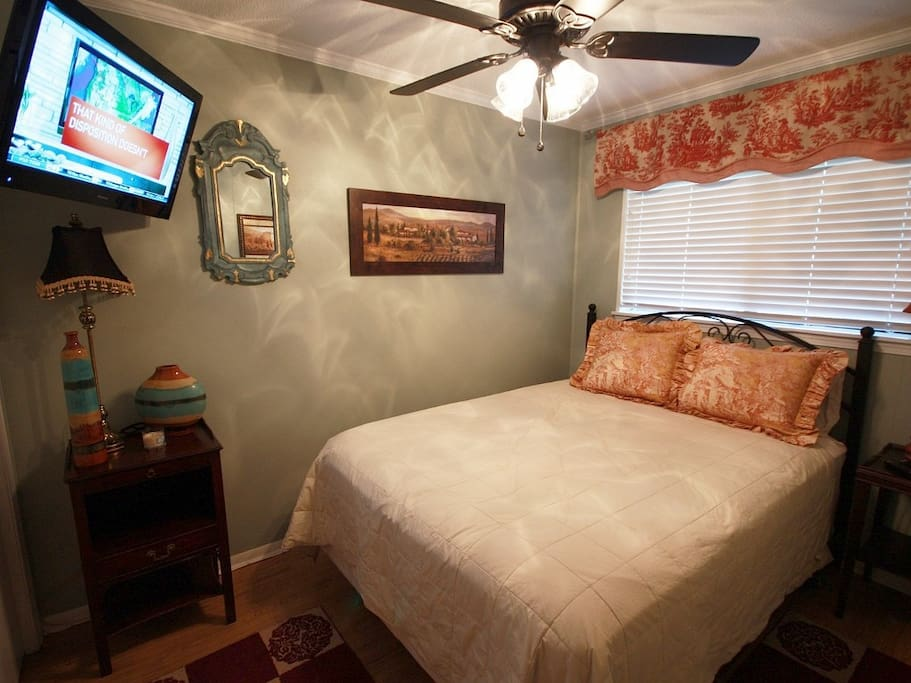Queen bed in the bedroom with wall mounted flat screen TV (cable channels included).