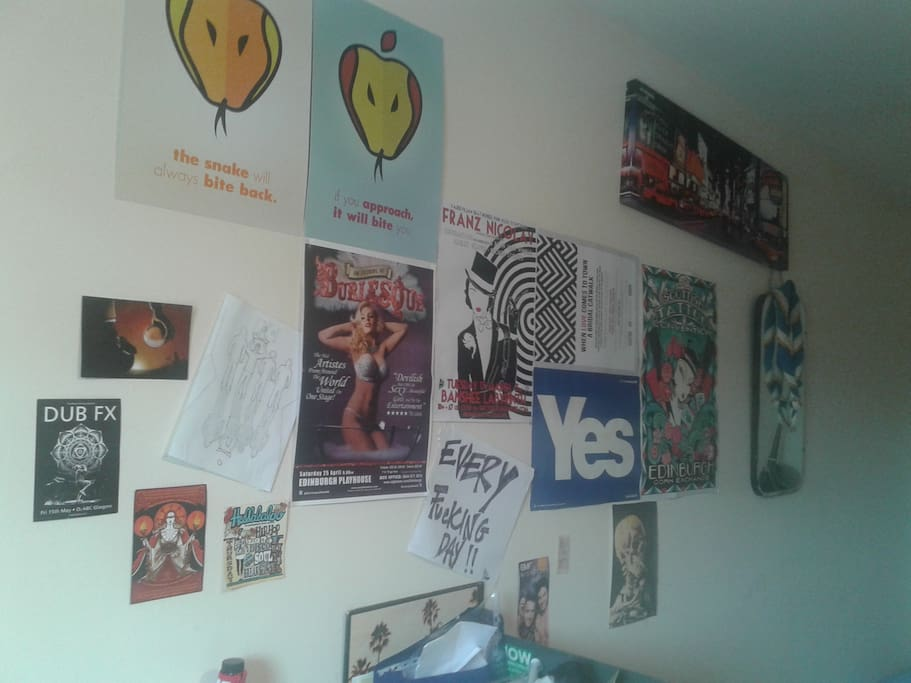some posters on the wall, also mirror in the room