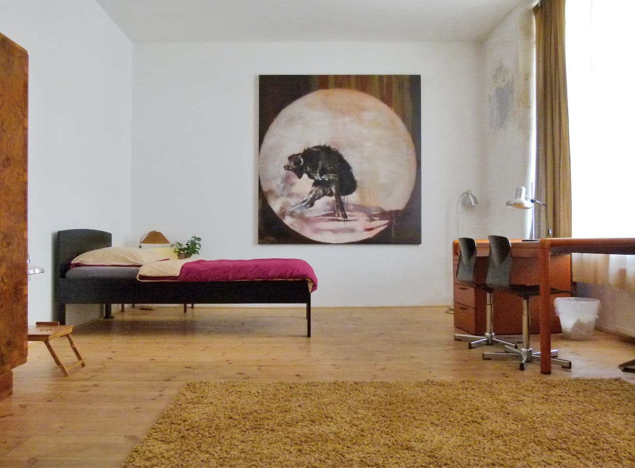 A large urban room with stylish furniture and Fine art.