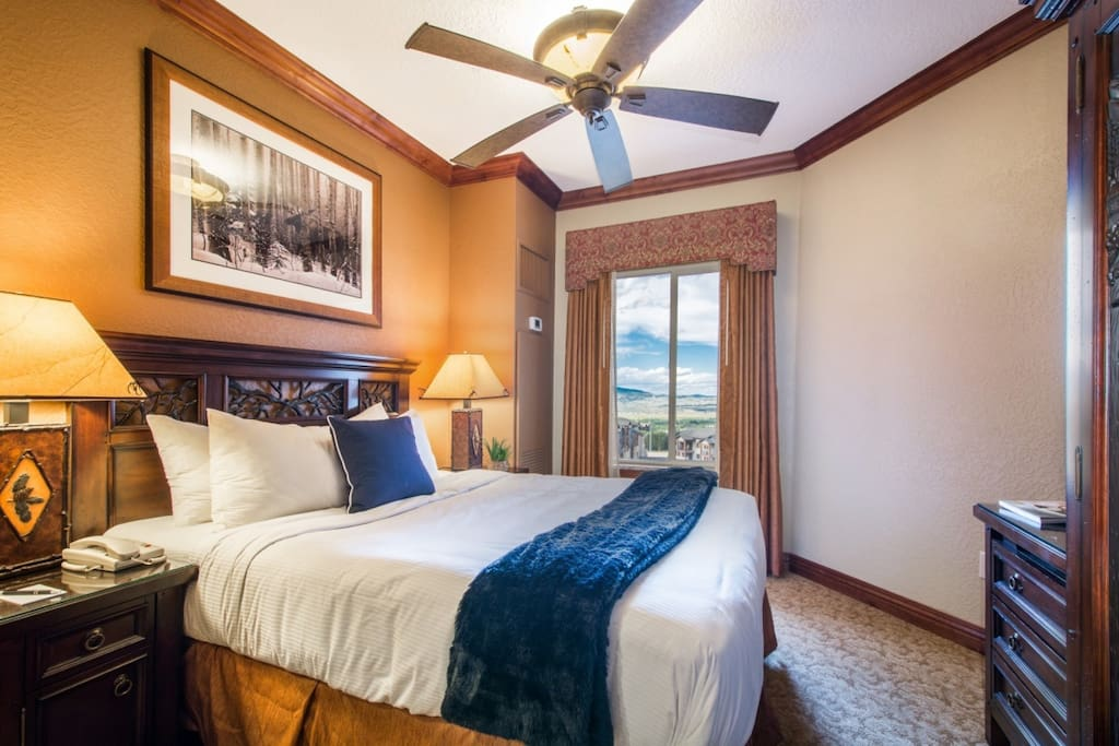 """The master bedroom featuring a queen size bed with luxury bedding/linens and a 28"""" flat screen TV is separated by pocket doors from the living area."""
