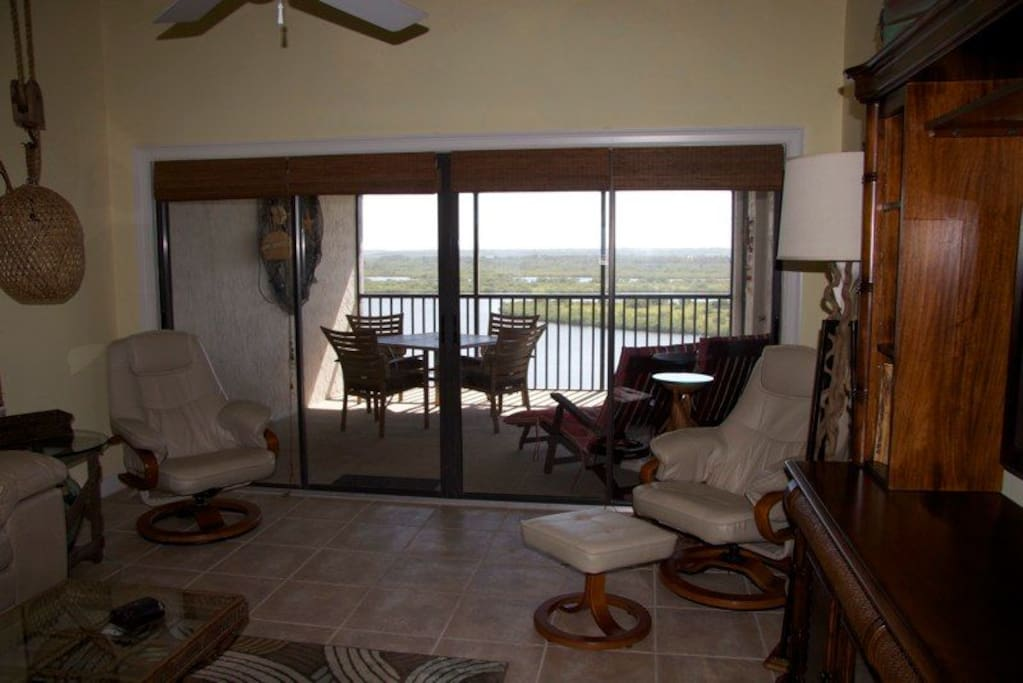View from living area onto screened in large back patio with estuary views